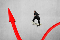 Businessman skateboarding on red arrow pointing up with concrete Stock Image