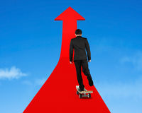Businessman skateboarding on red arrow in sky Royalty Free Stock Images