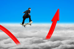 Businessman skateboarding on red growing arrow graph with sky cl Royalty Free Stock Photos