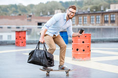 Businessman skateboarding on the rooftop Royalty Free Stock Image