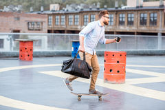 Businessman skateboarding on the rooftop Stock Image