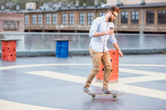Businessman skateboarding on the rooftop Stock Photos