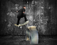 Businessman skating on money skateboard across metal euro symbol Royalty Free Stock Images