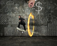 Businessman skating on money skateboard through fire circle with Stock Photography