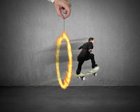 Businessman skating on money skateboard through fire circle Royalty Free Stock Photo