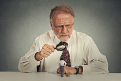 Businessman skeptically looking at small employee through magnifying glass Stock Photography