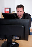 Businessman slamming on computer monitor Royalty Free Stock Photography