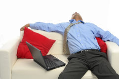 Businessman sleeping. Businessman with laptop sleeping, isolated in white Royalty Free Stock Photo