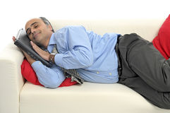 Businessman sleeping. Businessman with laptop sleeping in a couch isolated in white Stock Photos
