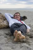 Businessman sleeping on a beach Stock Images