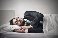 Businessman sleeping into bed Stock Image