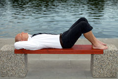 Businessman sleeping on bench with hands behind head Stock Photography