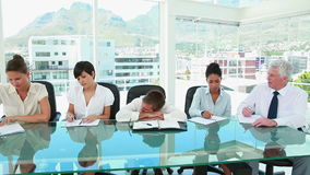 Businessman sleeping while colleagues are working Stock Image