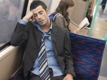 Businessman Sleeping In Commuter Train. Businessman with loosened tie sleeping in commuter train Royalty Free Stock Photo