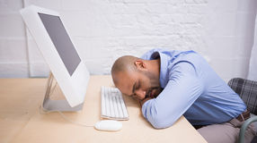 Businessman sleeping by computer at desk Stock Photos