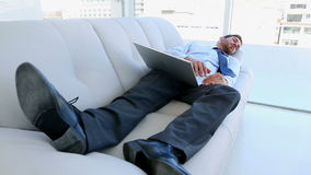 Businessman sleeping on couch with his laptop. In the office stock video