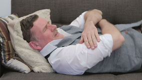 Businessman sleeping on couch in shirt and vest stock footage