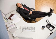 Businessman sleeping at desk with feet up stock photo