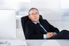 Businessman sleeping at desk in office. Mature Businessman Sleeping With Computer At Desk In Office Stock Photo