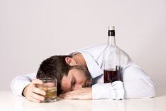 Businessman sleeping drunk of whiskey at desk on clear background Royalty Free Stock Photo