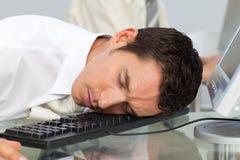 Businessman sleeping on a keyboard Royalty Free Stock Photos
