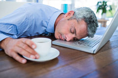 Businessman sleeping on laptop computer and touching coffee cup. In office Royalty Free Stock Images