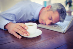 Businessman sleeping on laptop computer and touching coffee cup. In office Royalty Free Stock Image