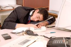 Businessman sleeping at office. Businessman sleeping in his office at table with computer Royalty Free Stock Photo