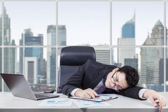 Businessman sleeping in office with laptop on desk. Caucasian businessman wearing formal suit and sleeping in the office with laptop and financial graph on the Royalty Free Stock Photo