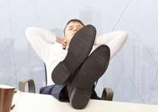 Businessman sleeping at the office. Businessman sleeping. Businessman reclining with his feet up on desk in office Royalty Free Stock Photos