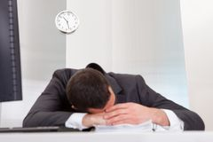 Businessman sleeping at the office. Successful businessman sleeping at desk it the office Stock Image