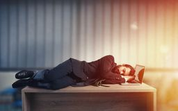 Businessman sleeping over a desk due to overwork Royalty Free Stock Image