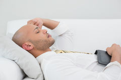 Businessman sleeping on sofa with digital tablet at home Royalty Free Stock Photos