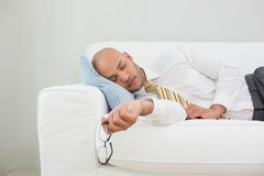 Businessman sleeping on sofa at home Royalty Free Stock Images