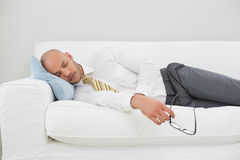 Businessman sleeping on sofa at home Stock Image