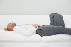 Businessman sleeping on sofa at home Stock Photography