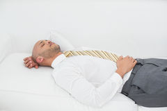 Businessman sleeping on sofa at home Royalty Free Stock Image