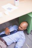 Businessman sleeping under desk Stock Image