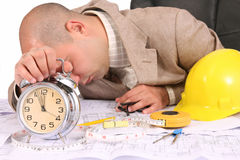 A businessman sleepy with architectural plans. At desk Stock Photo