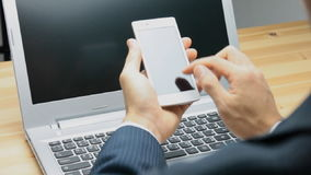 Businessman Slide Smartphone or Mobile Phone with Laptop Background stock video