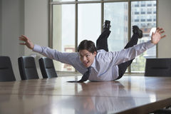 Businessman Sliding On Conference Table Royalty Free Stock Photography