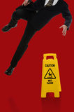 Businessman Slipping on Wet Floor. In front of caution sign over red background Stock Photo