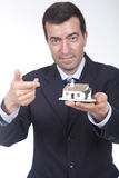 Businessman with a small house in his hand Royalty Free Stock Photo
