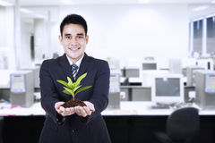 Businessman with small plant Royalty Free Stock Photo