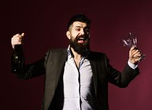 Businessman in smart suit tasting champagne on purple background. Man with smiling face and beard holding glasses and bottle. Connoisseur ready to drink Royalty Free Stock Images