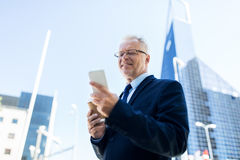 Businessman with smartphone and coffee in city Royalty Free Stock Photos
