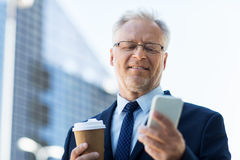 Businessman with smartphone and coffee in city Stock Images
