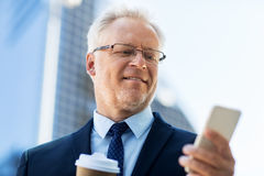 Businessman with smartphone and coffee in city Royalty Free Stock Images