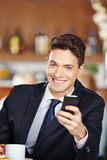 Businessman with smartphone in coffee shop Stock Photo