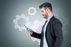 Businessman with smartphone, cogs sketch. Side view of bearded young businessman looking at his smartphone standing near gray wall with cogs sketch on it stock photo